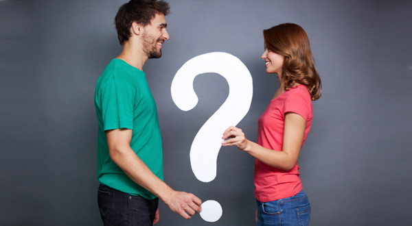 Portrait of young couple holding paper question mark and looking at on another