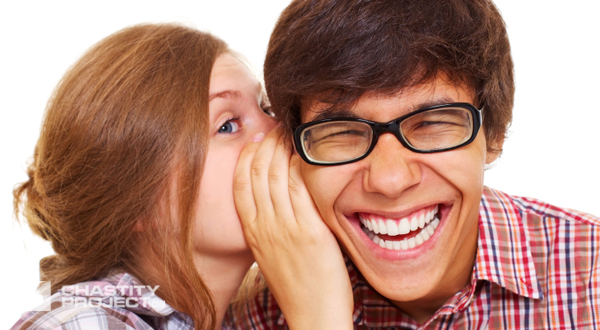 Pretty girl talking secret to young man in his ear, man laughing over isolated background