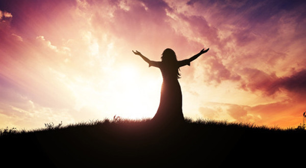 Woman lifting her hands up at sunset